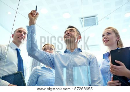 business, people, teamwork and planning concept - smiling business team writing something no notice board with marker in office