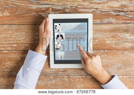 business, education, people, internet and technology concept - close up of male hands pointing finger to webpage article on tablet pc computer screen and coffee cup at table