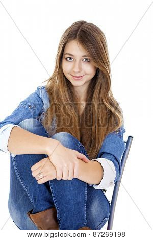 Portrait young girl in a jacket and blue jeans sitting on a chair, isolated on white