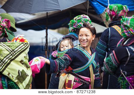 Portrait of tribal Hmong woman with baby in national clothes, Vietnam