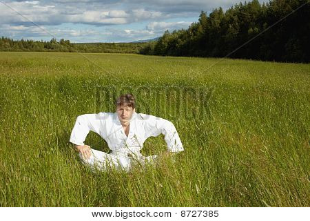 Young Man Sits In A Grass