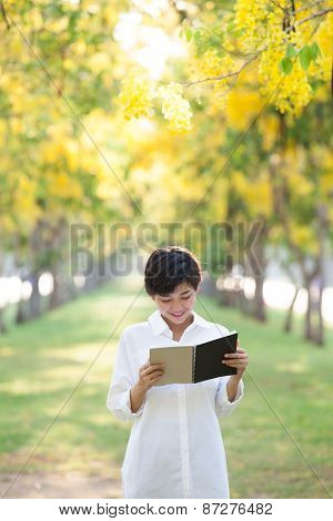 Portrait Of Young Beautiful Asian Woman Standing In Yellow Flowers Blooming Park Summer Season And R