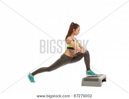 Beautiful athletic girl exercising on stepper