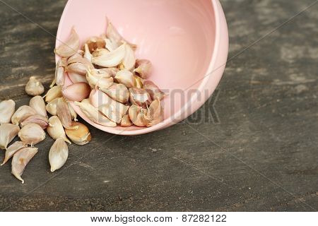 Garlic In A Pink Bowl On A Background Of Wood