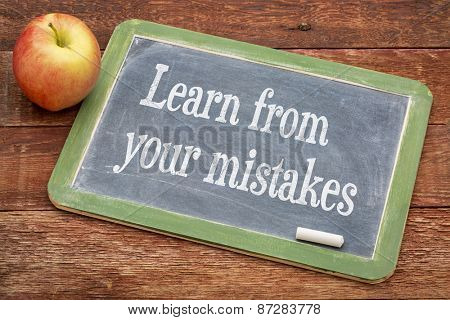 Learn from your mistakes - motivational words on a slate blackboard against red barn wood