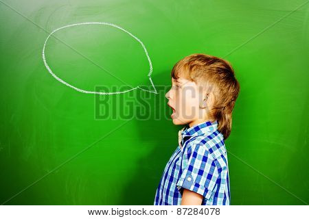 Smart schoolboy stands at the blackboard in the classroom. Education. New idea.