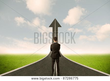 Businessman lokking at 3d road upgoing arrow concept