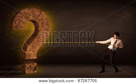 Business man pulling a big solid question mark stone concept on background
