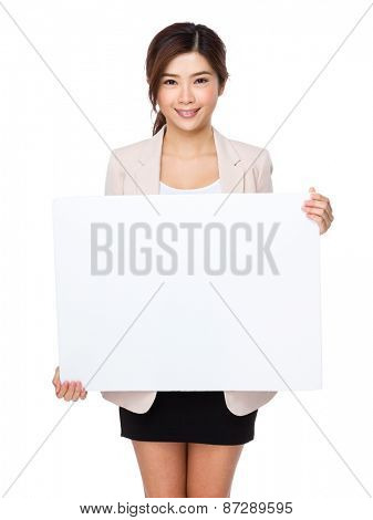 Young beautiful woman pointing blank billboard
