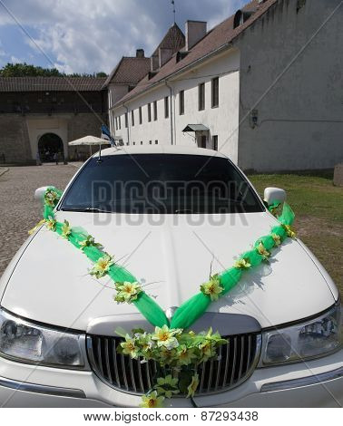 White wedding limousine in the yard of fortress Narva Estonia - a traditional place of wedding cerem