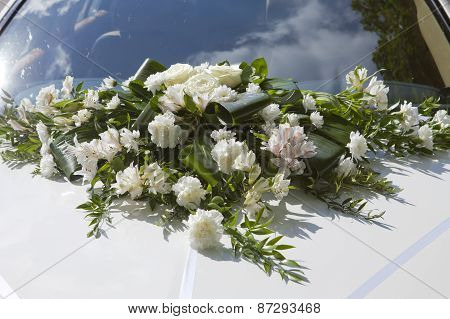 Wedding bouquet on a cowl of the white car