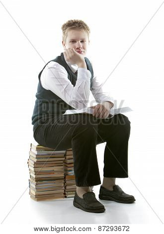 The schoolboy in a school uniform sits on a pack of books with the opened book in hands