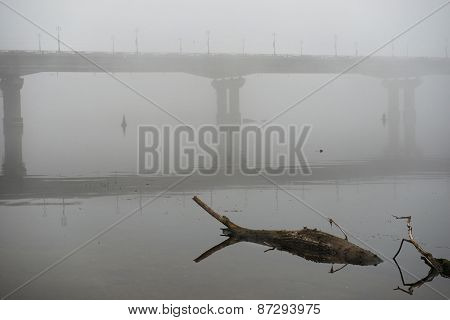 Bridge Through River In Misty Morning