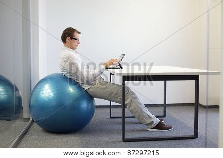 Relaxed position - young man on stability ball at desk working  with tablet