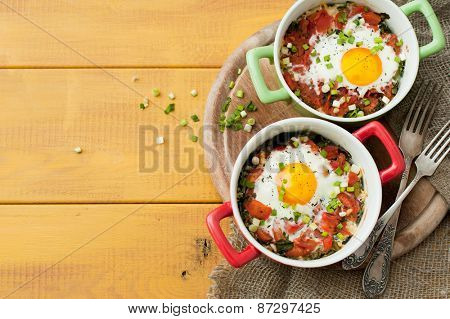 Baked eggs with tomatos and spinach on wooden background
