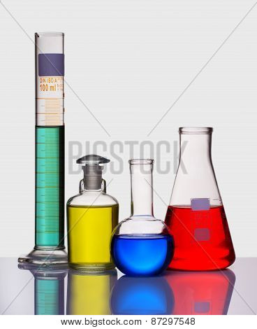 Volumetric Laboratory Glassware Containing Colored Liquids Isolated Over White Background