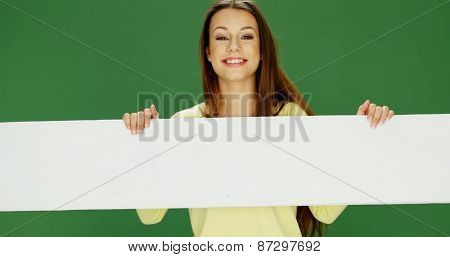 Smiling woman holding a long blank white horizontal banner in her hands looking over the top with a friendly smile, over green