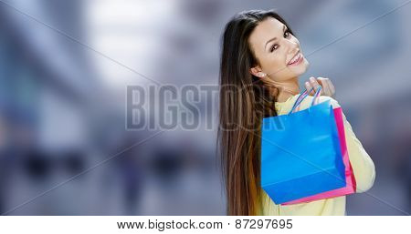 Happy attractive female shopper carrying her purchases in brightly colored carrier bags turning to smile over her shoulder at the camera