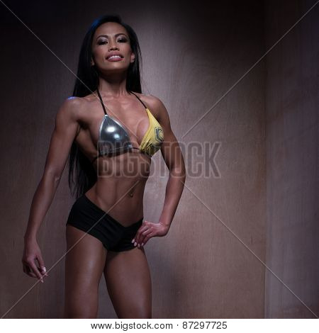 Portrait of a Young Bodybuilder Woman Posing in Sexy Fitness Outfit with Both Hands on her Hair and Smiling at the Camera on a Brown Wooden Wall Background.
