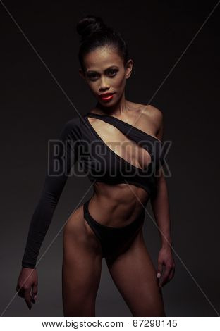 Portrait of a Sexy Young Woman Posing in Black Leotard While Looking at the Camera on a Gray Background.