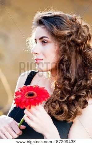 Portrait of young beautiful woman holding a red flower