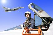 stock photo of aerialist  - The military pilot in the plane in a helmet in dark blue overalls against the blue sky - JPG