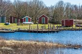 stock photo of vegetation  - Red wooden boat houses with wooden bridges in front - JPG