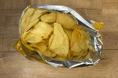 stock photo of potato chips  - potato chips in an open bag on a wooden table - JPG