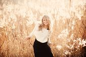 stock photo of pullovers  - Portrait of a beautiful young blonde girl in a field in white pullover laughing - JPG