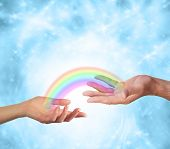 image of soulmate  - Female hand facing up and male hand facing up with a transparent rainbow connecting them together on a sparkling blue energy formation background - JPG