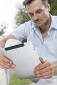 foto of telecommuting  - Young man using digital tablet in park - JPG
