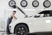 pic of car repair shop  - Full length side view of male mechanic examining car engine in repair shop - JPG