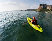 stock photo of kayak  - Lady with backpack paddling the kayak in the calm bay at sunny day - JPG