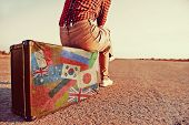 foto of old suitcase  - Tourist woman sitting on a suitcase on road - JPG