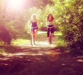 picture of bike path  - two girls riding bikes on a path in a park full of trees toned with a retro vintage instagram filter effect app or action  - JPG