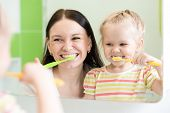 picture of teething baby  - Mom with child look at reflection in mirror brushing teeth at bathroom - JPG