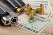 stock photo of corruption  - detail of gun with bullet on US dollar banknotes crime or corruption concept - JPG