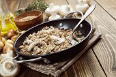 foto of porridge  - Buckwheat porridge with champignons in a metal pot on the table - JPG