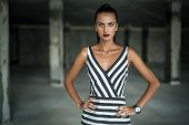 stock photo of striping  - Fashion model in a striped dress on a background of industrial columns - JPG