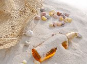 stock photo of suntanning  - bottle of suntan oil covered by sand with shells and cap - JPG
