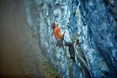 picture of climbing wall  - female rock climber climbs on a rocky wall