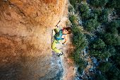 picture of cave woman  - female rock climber climbs on a rocky wall - JPG