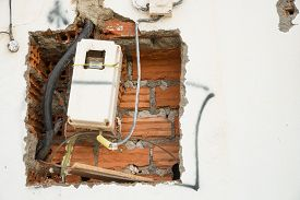 pic of electricity meter  - Unfinished wiring and electricity meter on a wall - JPG