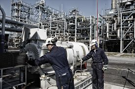 image of refinery  - oil and gas workers with machinery inside large refinery - JPG