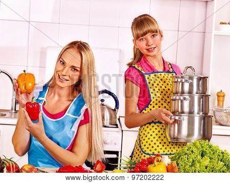Mother and daughter cooking food at kitchen.