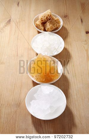 sugar types in white bowls, white wood table background