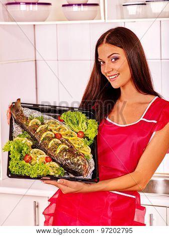 Happy woman prepare fish at oven-tray.