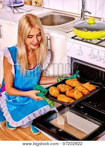 Young blond smilig woman bake cookies. Kitchen.