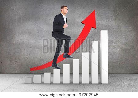 Businessman walking with his leg up against grey room