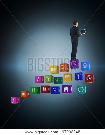 Handsome businessman standing using a laptop against blue background with vignette